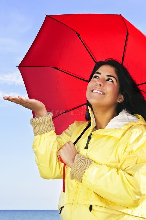 Belle jeune femme dans l'imperméable avec le parapluie image stock