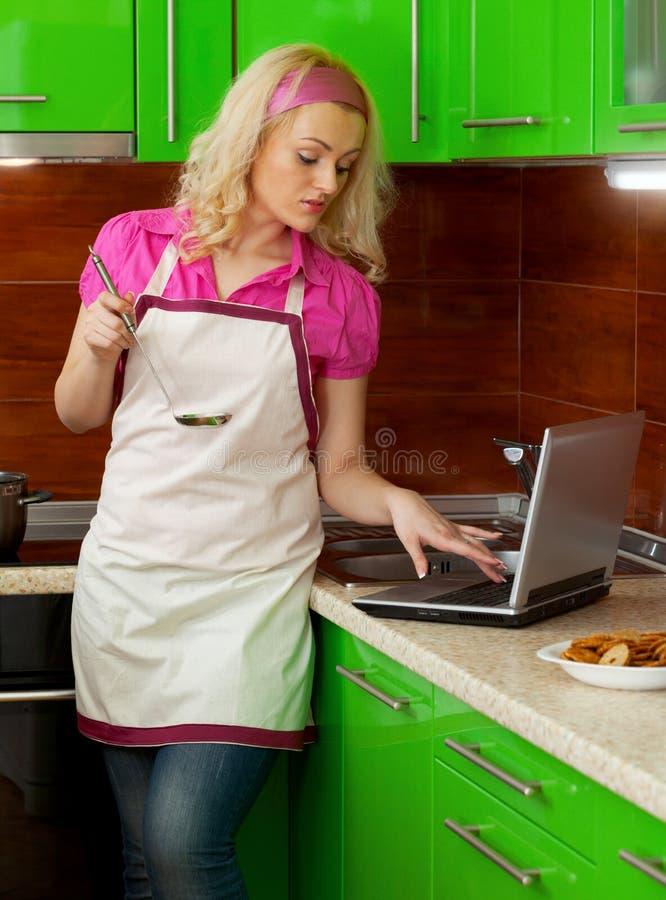 Belle jeune femme dans la cuisine utilisant un ordinateur portable photographie stock libre de droits
