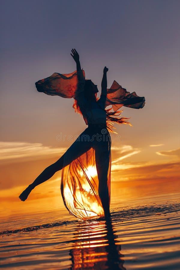 Belle jeune femme dans la danse de robe élégante sur l'eau au sunse image stock
