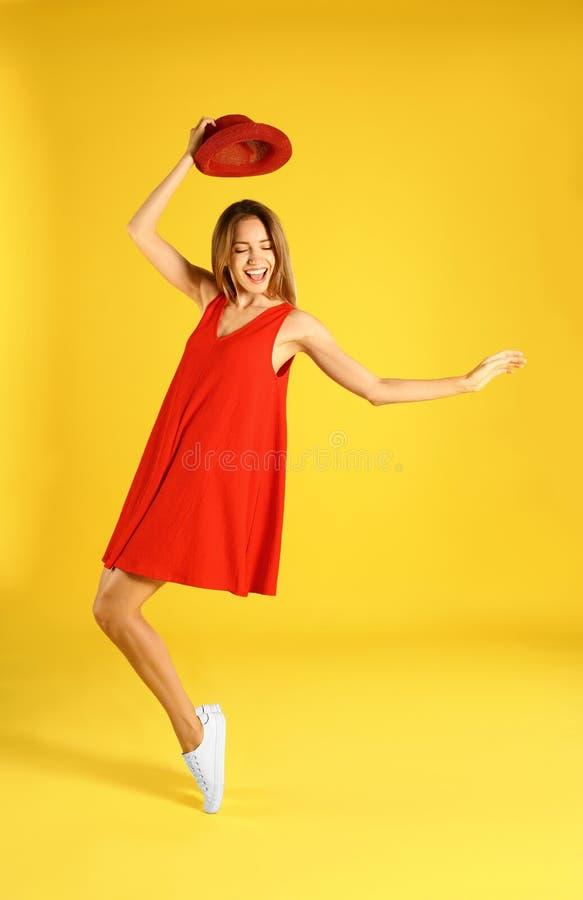Belle jeune femme dans la danse rouge de robe sur le jaune images stock