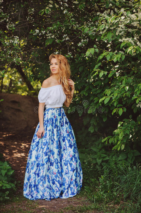 Belle jeune femme dans la maxi jupe bleue florale marchant au printemps photographie stock
