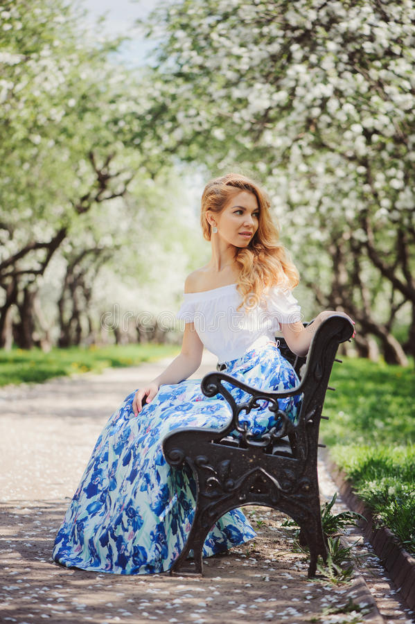 Belle jeune femme dans la maxi jupe bleue florale marchant au printemps image stock