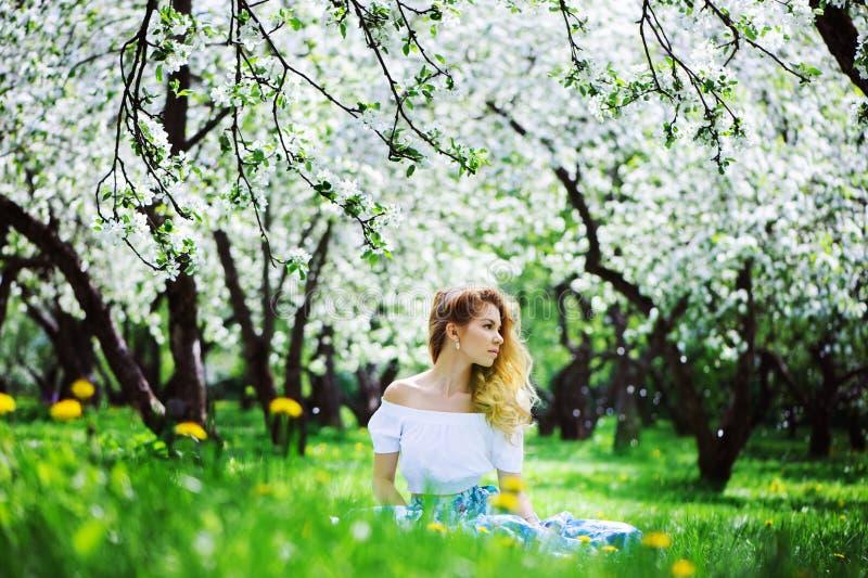 Belle jeune femme dans la maxi jupe florale marchant au printemps photographie stock libre de droits
