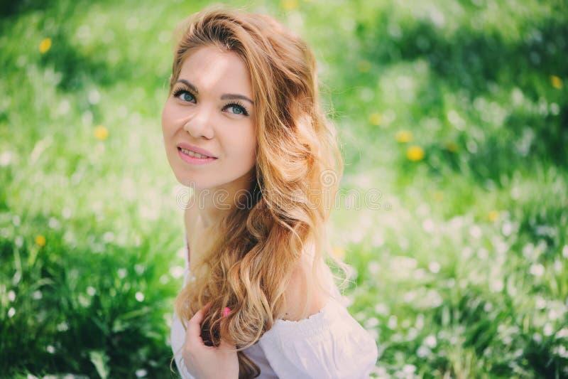 Belle jeune femme dans la maxi jupe florale marchant au printemps photographie stock
