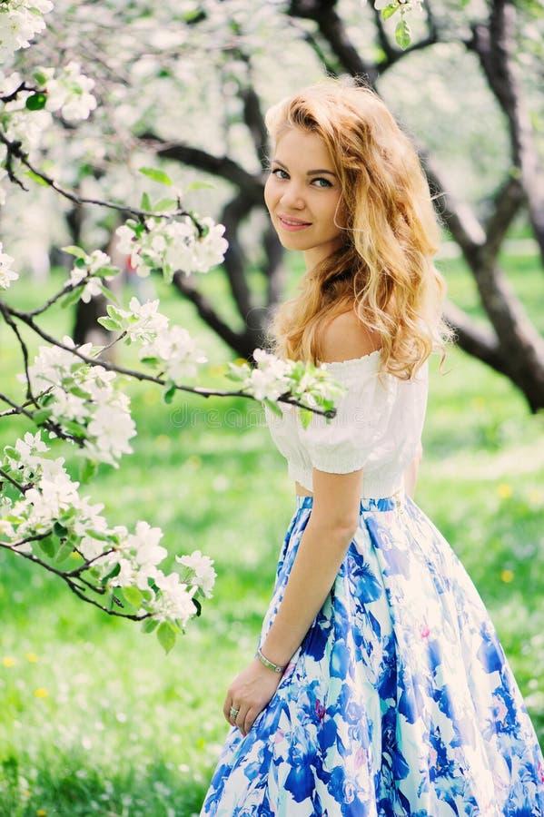 Belle jeune femme dans la maxi jupe florale marchant au printemps images stock