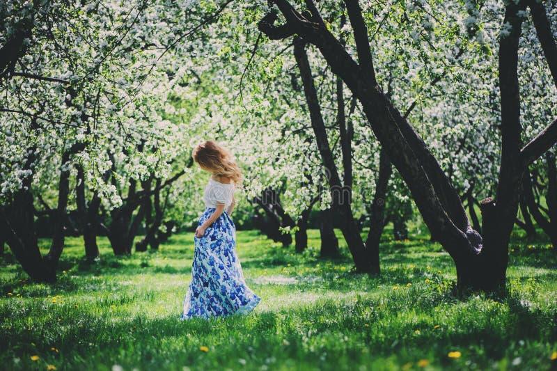 Belle jeune femme dans la maxi jupe florale marchant au printemps photo libre de droits