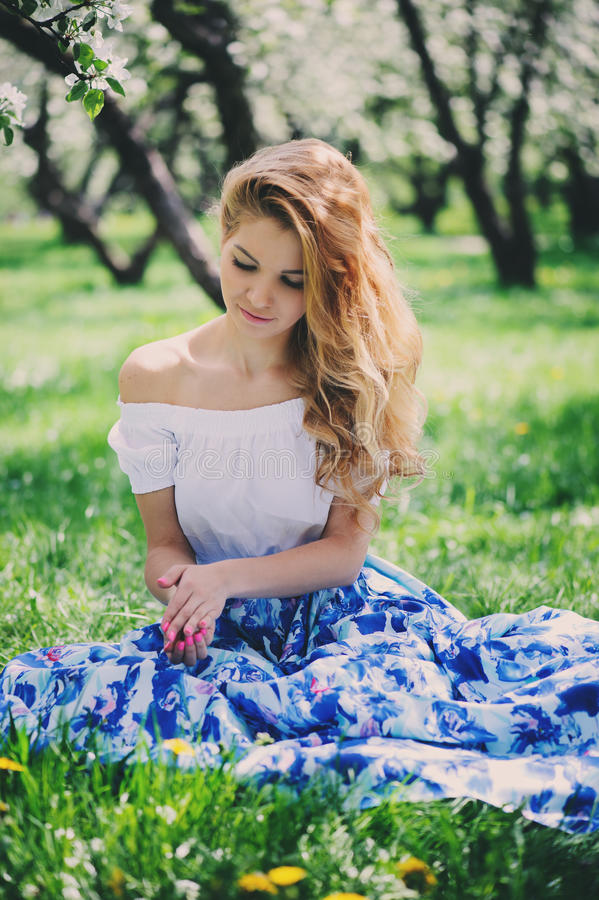 Belle jeune femme dans la maxi jupe florale marchant au printemps photos libres de droits