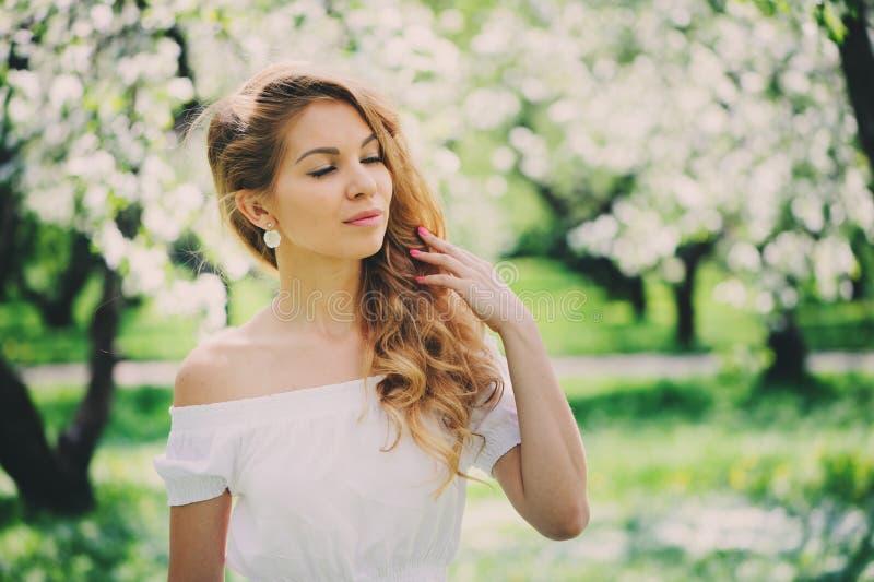 Belle jeune femme dans la maxi jupe florale marchant au printemps image stock