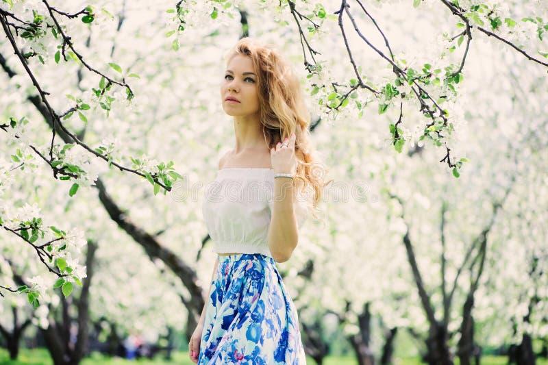 Belle jeune femme dans la maxi jupe florale marchant au printemps photo stock