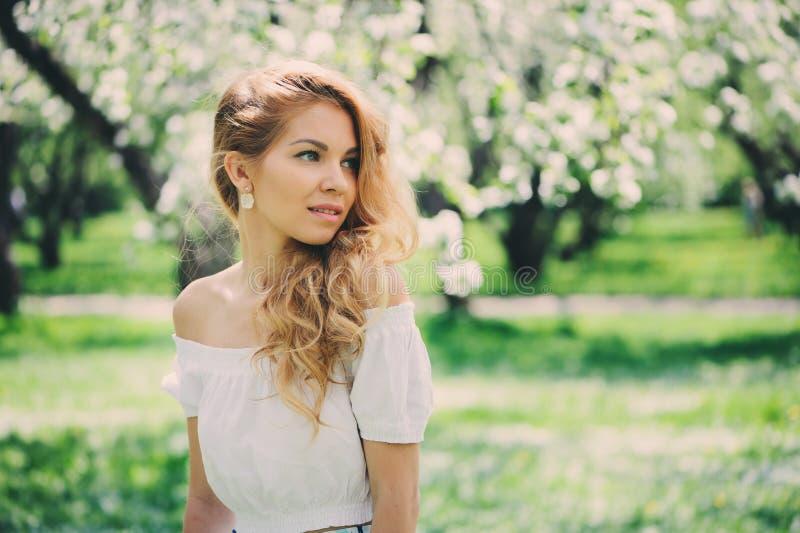 Belle jeune femme dans la maxi jupe florale marchant au printemps image libre de droits