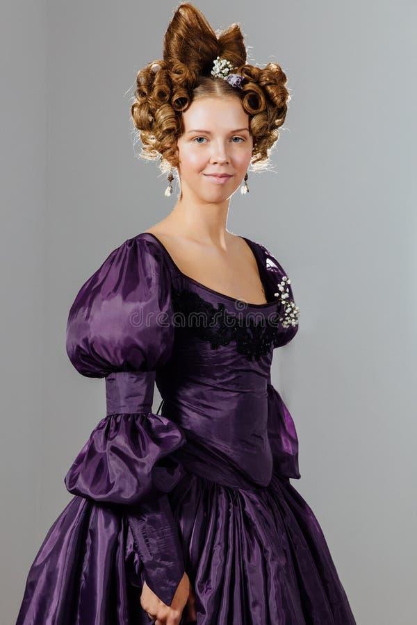 Belle jeune femme dans la robe de vintage avec des cheveux de concepteur Boule, égalisant la réception photographie stock