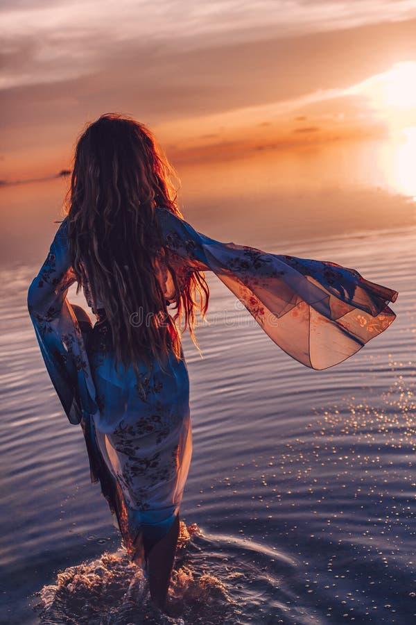 Belle jeune femme dans la robe elegan marchant sur l'eau au coucher du soleil photos libres de droits