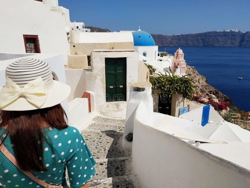 Belle jeune femme dans la robe pointill?e verte marchant ? Oia, rues de Santorini Maisons blanches, mer bleue photographie stock libre de droits