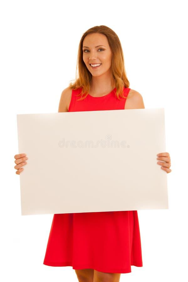Belle jeune femme dans la robe rouge tenant la bannière vide blanche pour le texte supplémentaire ou les graphiques d'isolement a photos stock