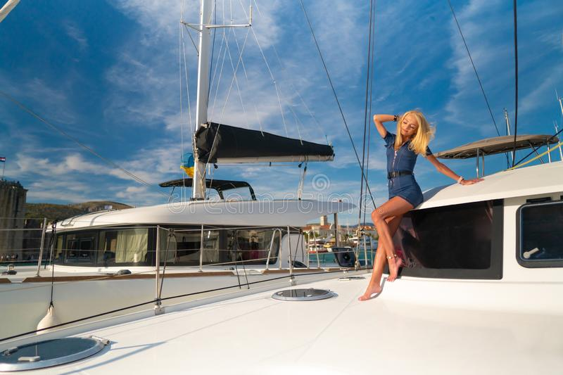 Belle jeune femme dans la tenue de détente se tenant sur un avant de yacht à la marina de Trogir, Croatie image libre de droits