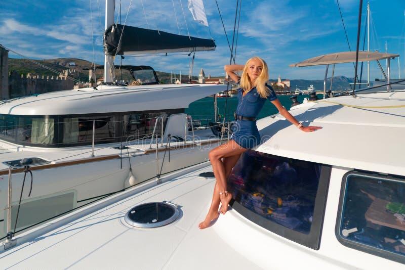 Belle jeune femme dans la tenue de détente se tenant sur un avant de yacht à la marina de Trogir, Croatie images stock