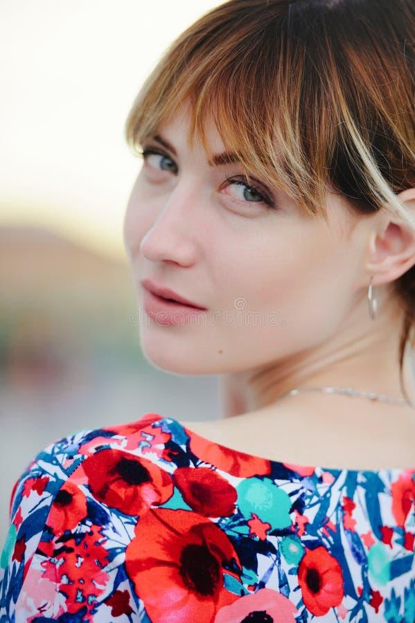Belle jeune femme dans la ville au coucher du soleil dans une robe, lumière chaude molle, confortable et aimable tendres image stock