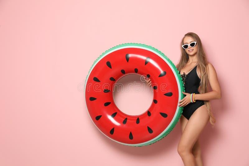 Belle jeune femme dans le bikini avec l'anneau gonflable sur le fond de couleur photo stock
