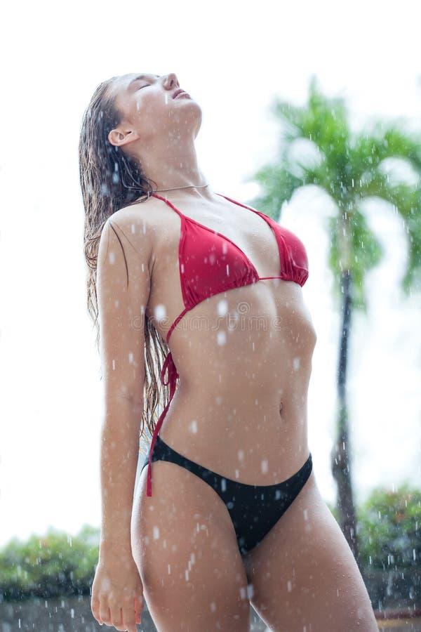 belle jeune femme dans le bikini se tenant et posant avec le palmier de noix de coco dehors pendant la saison de pluie femelle se image stock