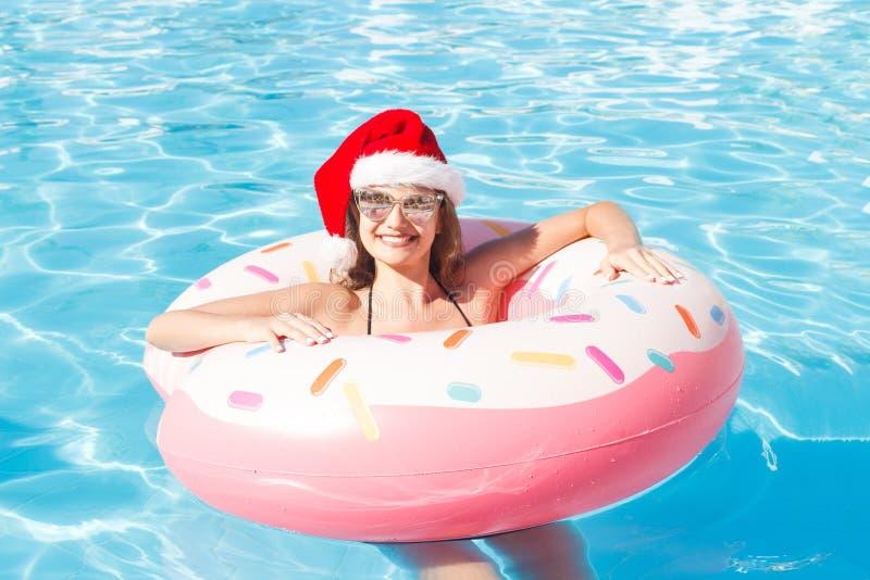 Belle jeune femme dans le chapeau de Santa Claus avec le cercle rose détendant dans la piscine bleue photos libres de droits