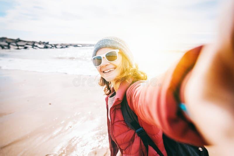 Belle jeune femme dans le chapeau et des lunettes de soleil marchant en hiver dessus photos libres de droits