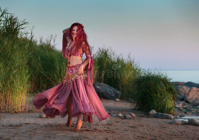 Belle jeune femme dans le costume oriental de danse par la mer image stock
