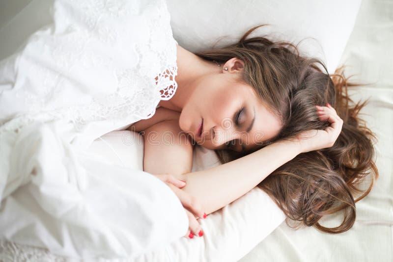 Belle jeune femme dans le lit, sommeil photos stock