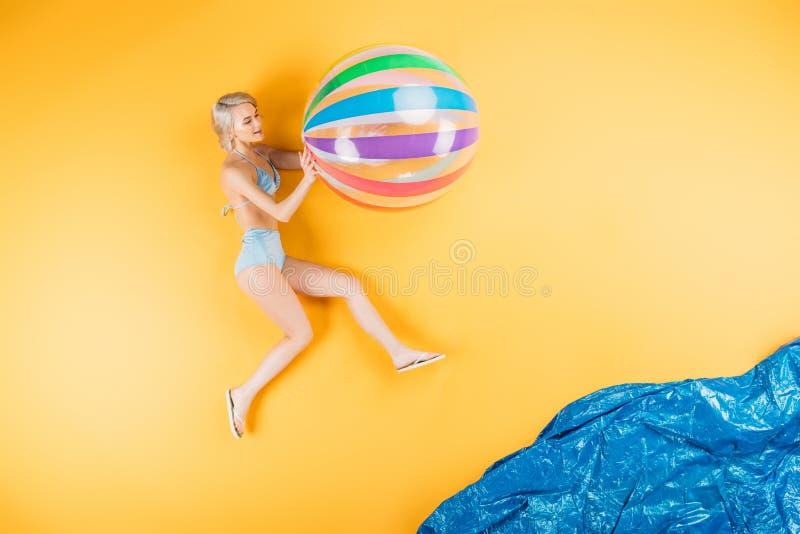 belle jeune femme dans le maillot de bain et bascules électroniques tenant la boule gonflable image libre de droits
