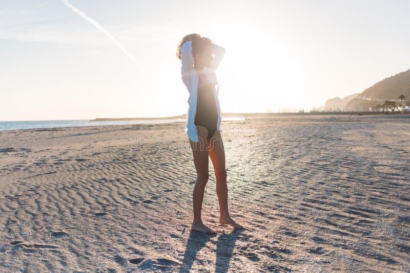 Belle jeune femme dans le maillot de bain sur la plage photographie stock