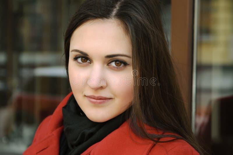 Belle jeune femme dans le manteau rouge sur l'air de plein photographie stock