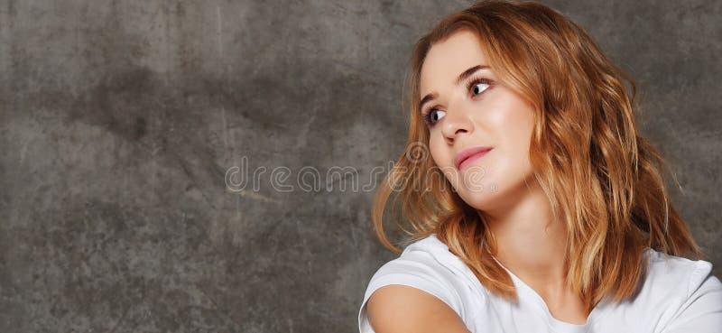 Belle jeune femme dans le T-shirt regardant loin la caméra d'isolement sur le fond de mur en béton photo stock