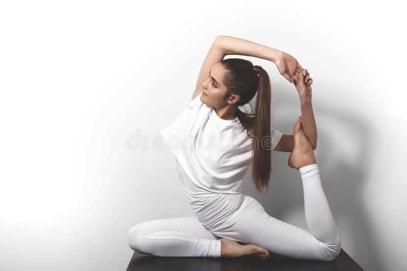 Belle jeune femme dans le yoga posant dans l'asana sur un fond de studio photos stock