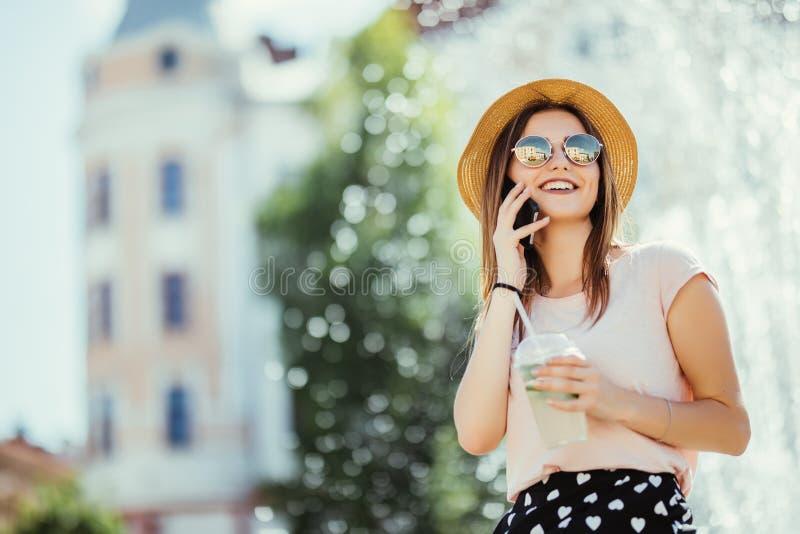 Belle jeune femme dans les lunettes de soleil et le chapeau en cocktail régénérateur potable de mojito de café tout en parlant au images stock