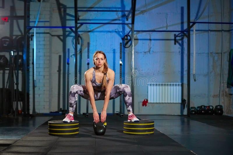 Belle jeune femme dans les vêtements de sport gris faisant l'exercice avec le poids Ajustement de croix photographie stock libre de droits