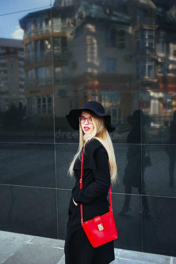 Belle jeune femme dans un manteau et un chapeau noir, verres rouges de port et un sac rouge marchant dans la ville Réflexion de photo libre de droits