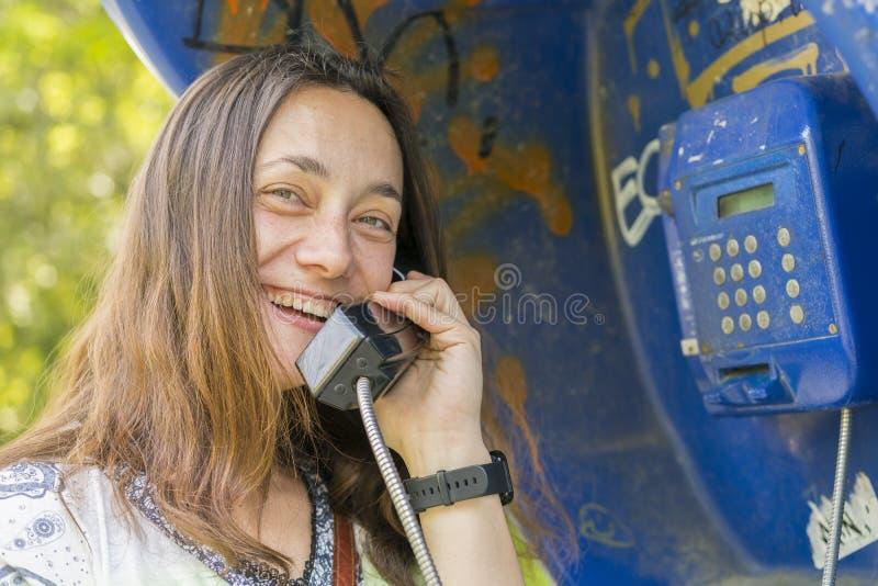 Belle jeune femme dans une cabine de téléphone La fille parle au t?l?phone de la cabine t?l?phonique jolie femme parlant par le p photo stock