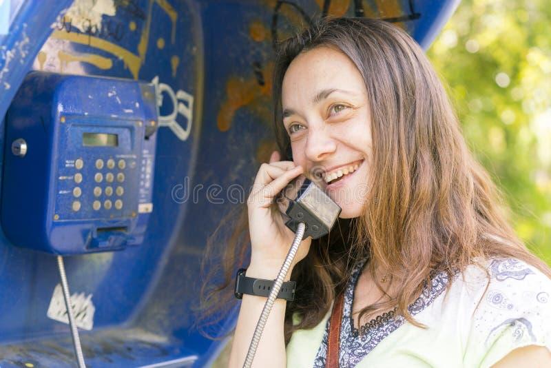 Belle jeune femme dans une cabine de téléphone La fille parle au t?l?phone de la cabine t?l?phonique jolie femme parlant par le p images libres de droits
