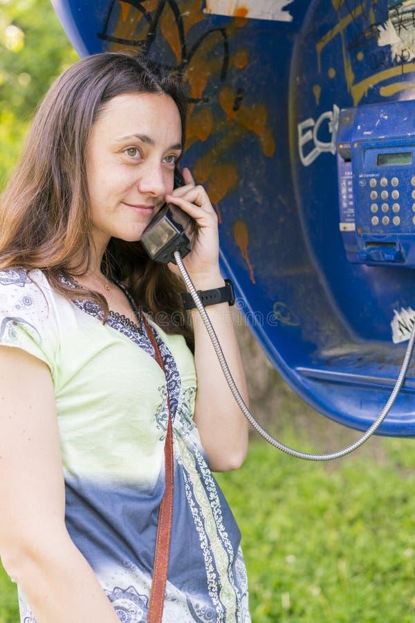 Belle jeune femme dans une cabine de téléphone La fille parle au t?l?phone de la cabine t?l?phonique femme parlant par téléphone  photos libres de droits