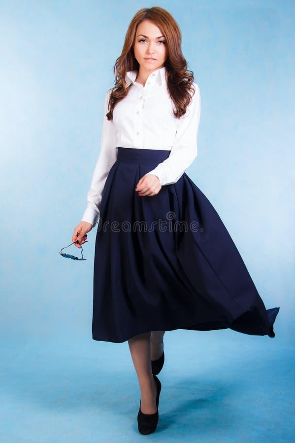Belle jeune femme dans une chemise blanche et une longue jupe bleue photos libres de droits