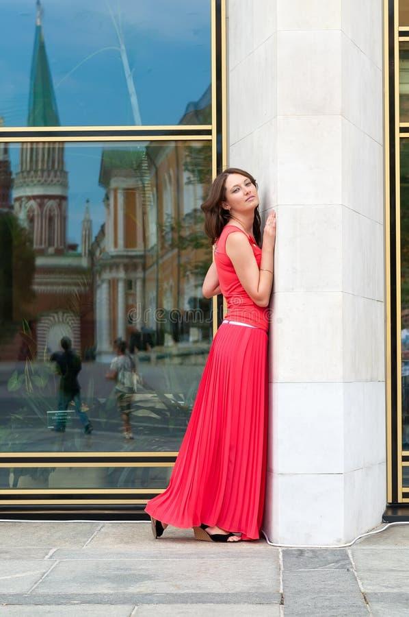 Belle jeune femme dans une longue robe de soirée rouge avec un train se tenant à côté du vieux mur images stock
