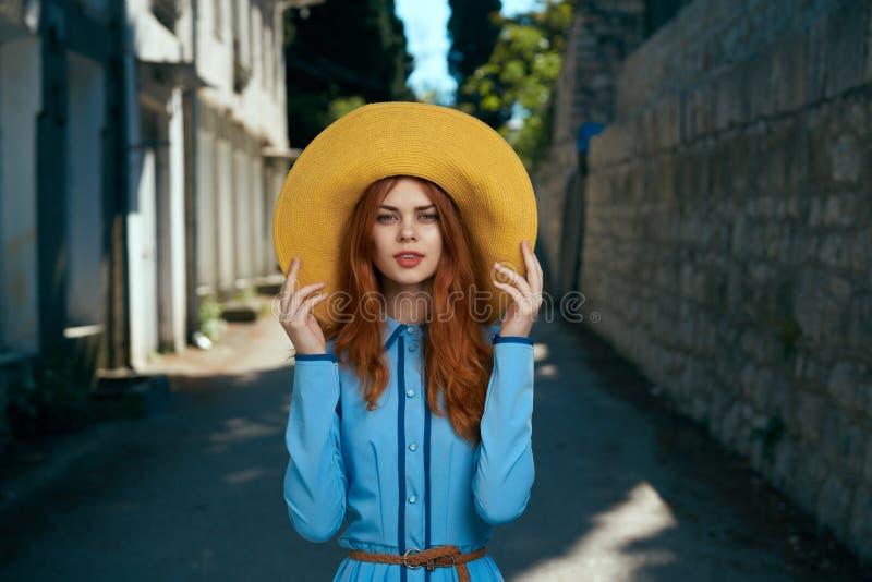 Belle jeune femme dans une robe bleue et dans un chapeau jaune dans une ruelle dans la ville images stock
