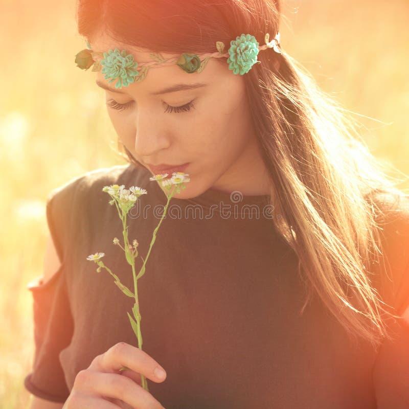 Belle jeune femme de boho à la lumière du soleil de fleur de prise de pré d'été photos stock