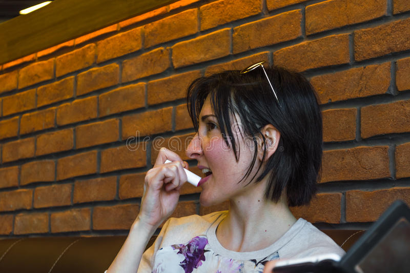 Belle jeune femme de brune appliquant le baume à lèvres sur ses lèvres photos libres de droits