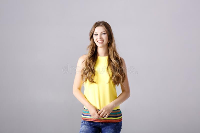 Belle jeune femme de brune avec de longs cheveux souriant et regardant l'appareil-photo photo libre de droits