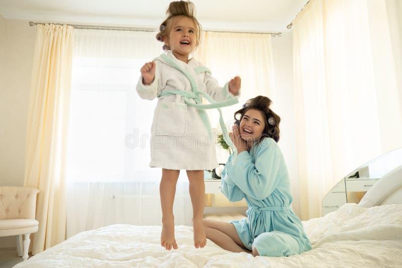 Belle jeune femme de brune avec le bébé sautant mignon sur le lit utilisant les peignoirs bleus avec des bigoudis ayant l'amuseme photo libre de droits