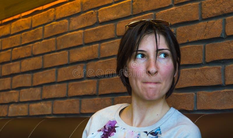 Belle jeune femme de brune avec les lèvres pressées se reposant au cafétéria photographie stock libre de droits