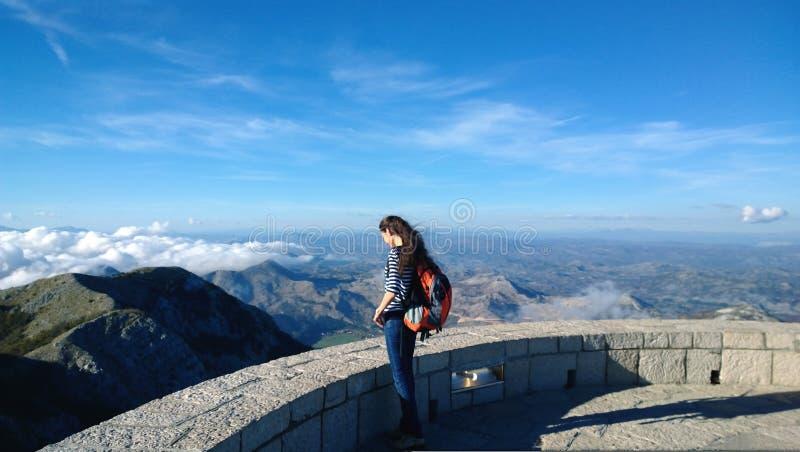 Belle jeune femme de brune avec de longs cheveux se tenant au bord d'une falaise avec un sac à dos chez le Njegos commémoratif photos libres de droits