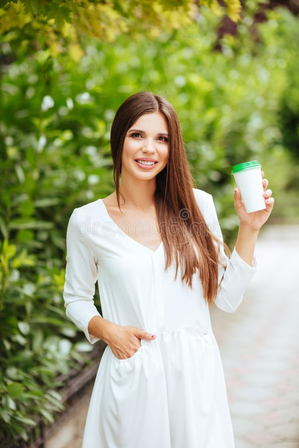Belle jeune femme de brune buvant du café à emporter en parc en été image libre de droits