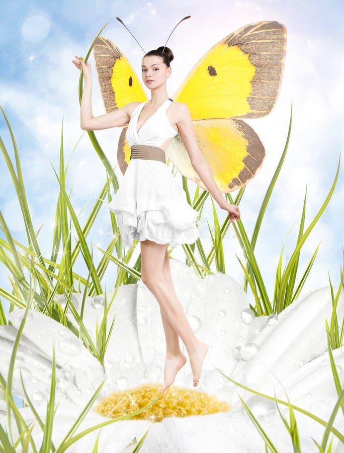 Belle jeune femme comme papillon sur la marguerite de ressort photographie stock libre de droits