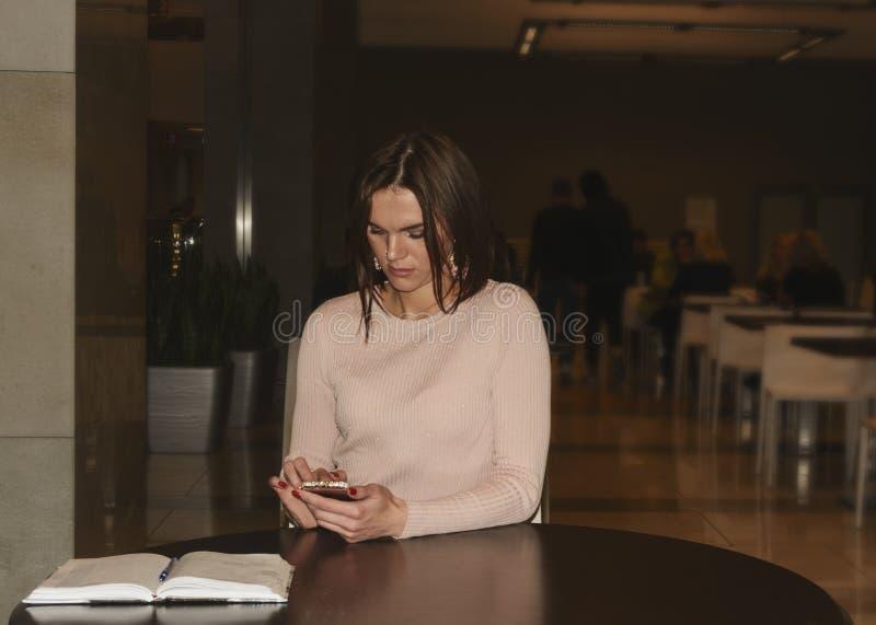 Belle jeune femme de brune s'asseyant à une table en bois ronde photo libre de droits